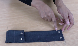 Colleen G Lea - Demonstrating how to hand sewing press studs.